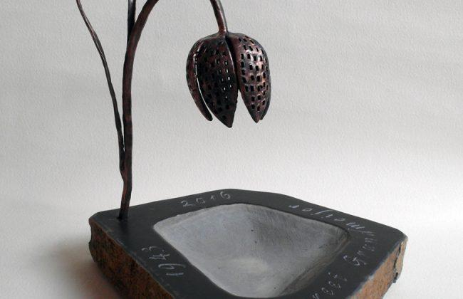 Bronzen ornament op schaal uit basalt